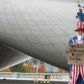 Uncle Sam at Chicago's Millennium Ball with a sign asking for National Debt money
