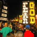 """""""Fear God"""" and """"You Still Need Jesus"""" signs in the Bourbon Street crowd in New Orleans, LA"""