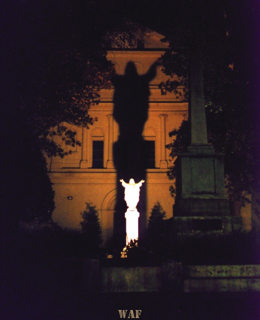 a spotlight highlighting a Jesus statue in the back courtyard of St. Louis Cathedral in the French Quarter in New Orleans, LA